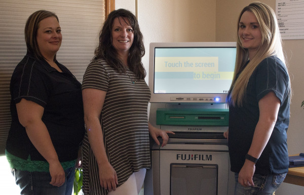 Three woman pose around a photo printing kiosk in an office.