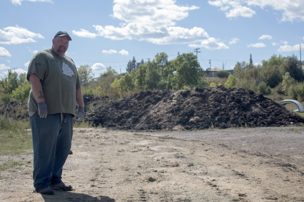 A man stands in front of a long and large pile of what appears to be dirt and compost.