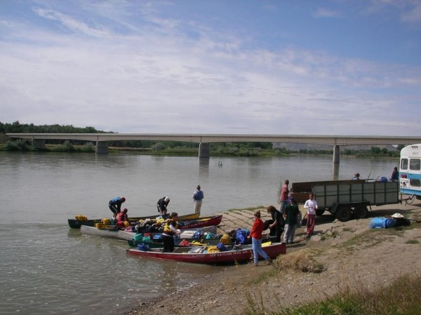 People mill around canoes that sit partially in a large river.