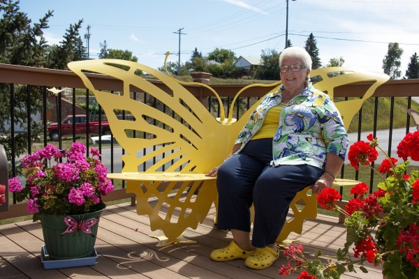 An older woman sits on a patio bench back by an intricate yellow butterfly cutout.