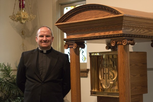 A man dressed in the black suit and white collar of a priest stands by a columned wood gazebo containing a gold box.