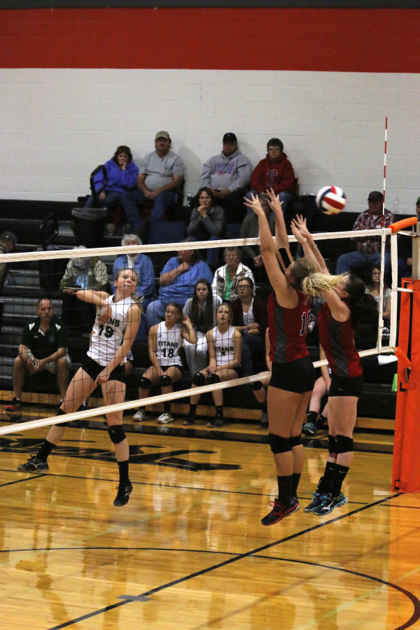 Two girls jump, hands tilted over a net, to block a volleyball that has sailed past them, while a player comes down from a spike on the other side.