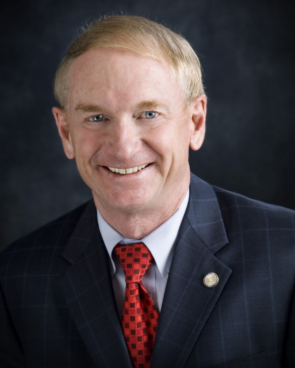 A politician stares at the camera dressed in a suit jacket, red tie and white collared shirt.