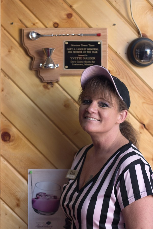 A smiling woman in a referee shirt and ball cap stands in front of a wooden plaque mounted on the wall in a sports bar.