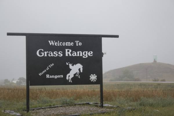 "A sign made of thick metal stands with the words ""Welcome to Grass Range"" punched out."