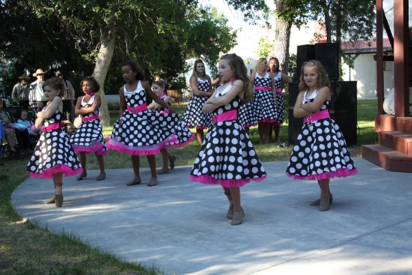 Young girls in black and white polka dotted dress prepare to dance on an outside cement patio.