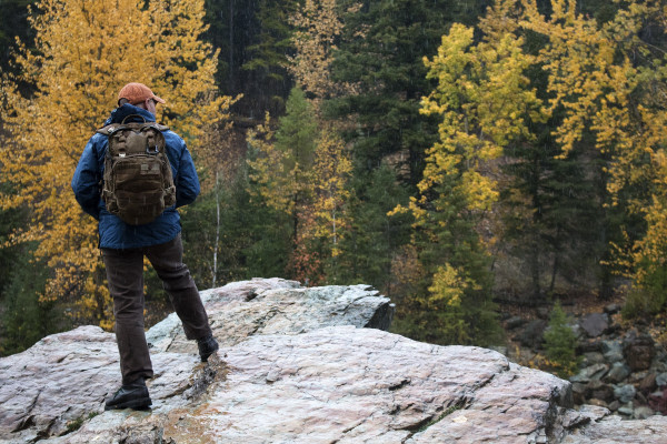A man wearing slick rain gear and a backpack stands on top of a large, wet boulder, looking away from the camera at the contrast of fall leaves and pine trees.