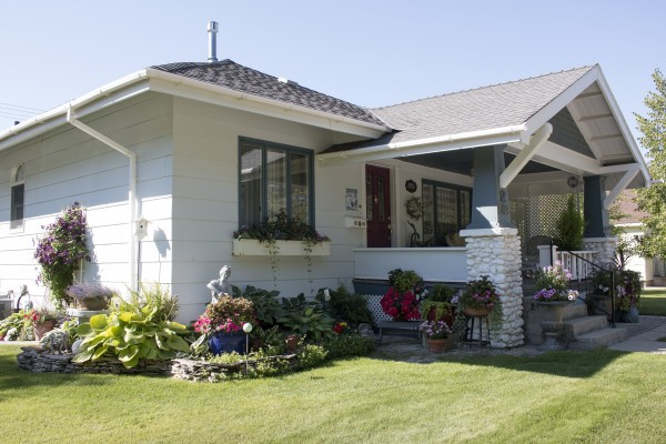 A white cottage-style house sits in the summer sun surrounded by a mowed lawn and blooming gardens.