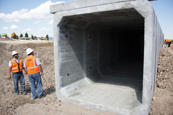 Two men in bright orange construction vests and hard had stand by a dark, square cement tunnel.