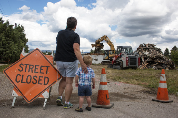 From the back, we can see a grandmother hugging her toddler grandson to her side as the two watch construction equipment tear the roof from a small, one-story building.