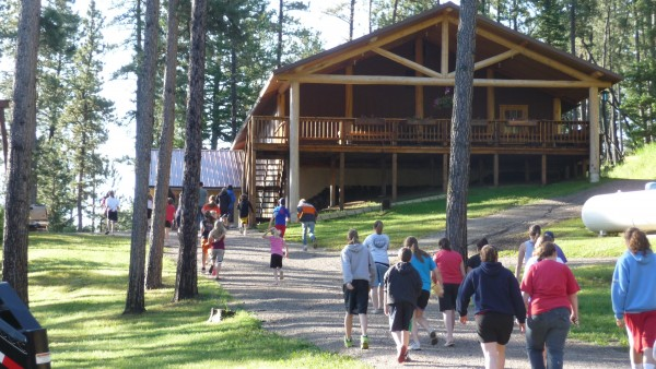 Kids walk up a wooded hill to a large log hall during the summer.