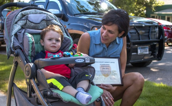 A woman holding an honorary wooden plaque crouches next to a toddler strapped into a stroller.