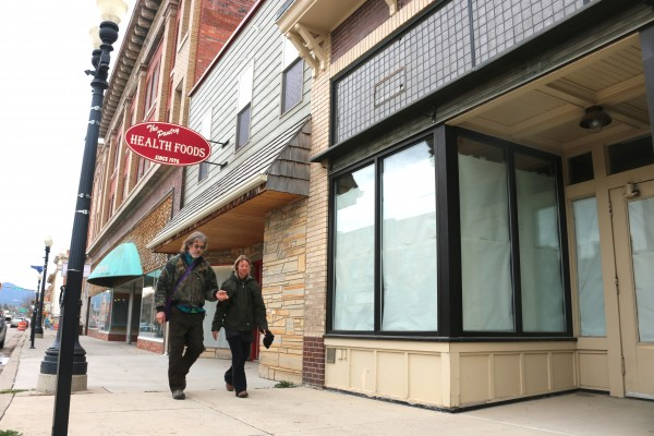 A couple walks down Main Street Thursday past windows of vacant storefronts.