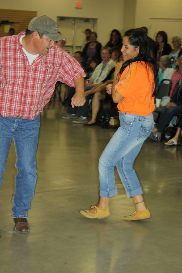 A man and woman are caught in a whirling moment with grasped hands as a crowd watches the smiling, dancing pair.
