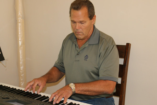 A man sits in a wooden dining-room chair and plays the piano.