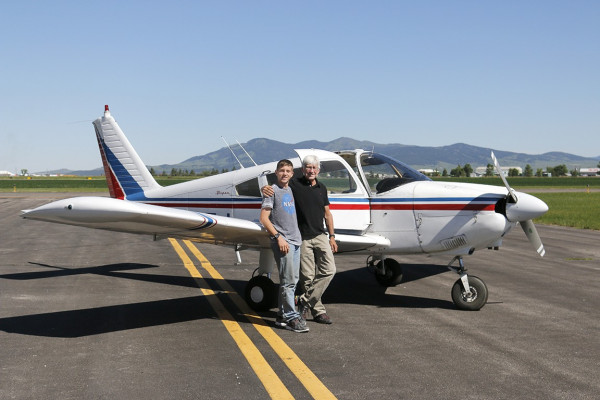 Grandson and grandfather stand in front of a small private plane on a runway.