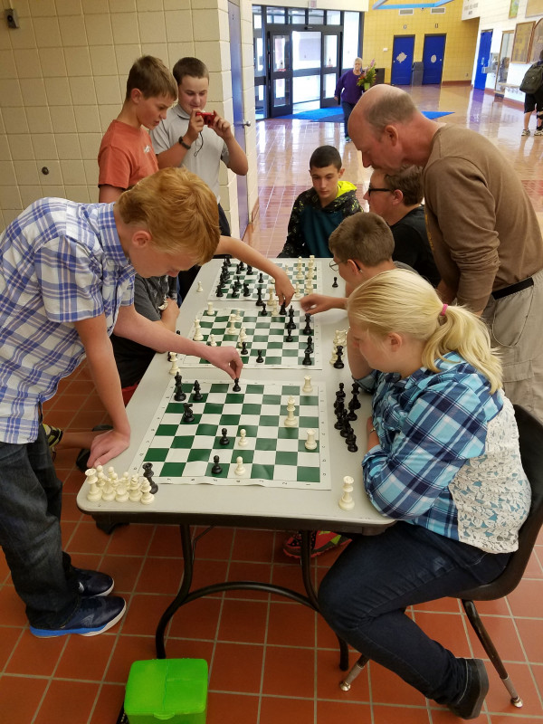 Kids crowd around a long table lined with chess boards as a middle-aged male teacher makes moves as the competitor.