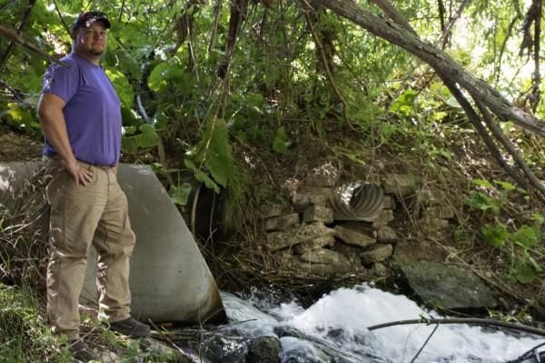 A man stands by a culvert spilling water into a stream.
