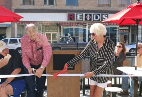 Arts and Entertainment District Association representatives Duane Ferdinand, left, and Carol Woolsey cut the ribbon to officially dedicate Lewistown's new parklet in front of Studio Milan on Main Street. The goal of the parklet is to encourage activity downtown and support local businesses. Photo by Charlie Denison